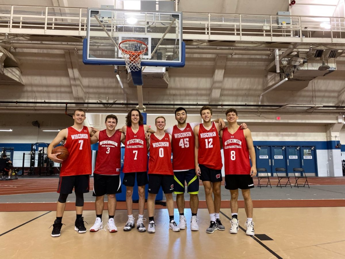A photo of 7 players of the Men's Club Basketball team in front of a hoop at the Camp Randall Sports Center