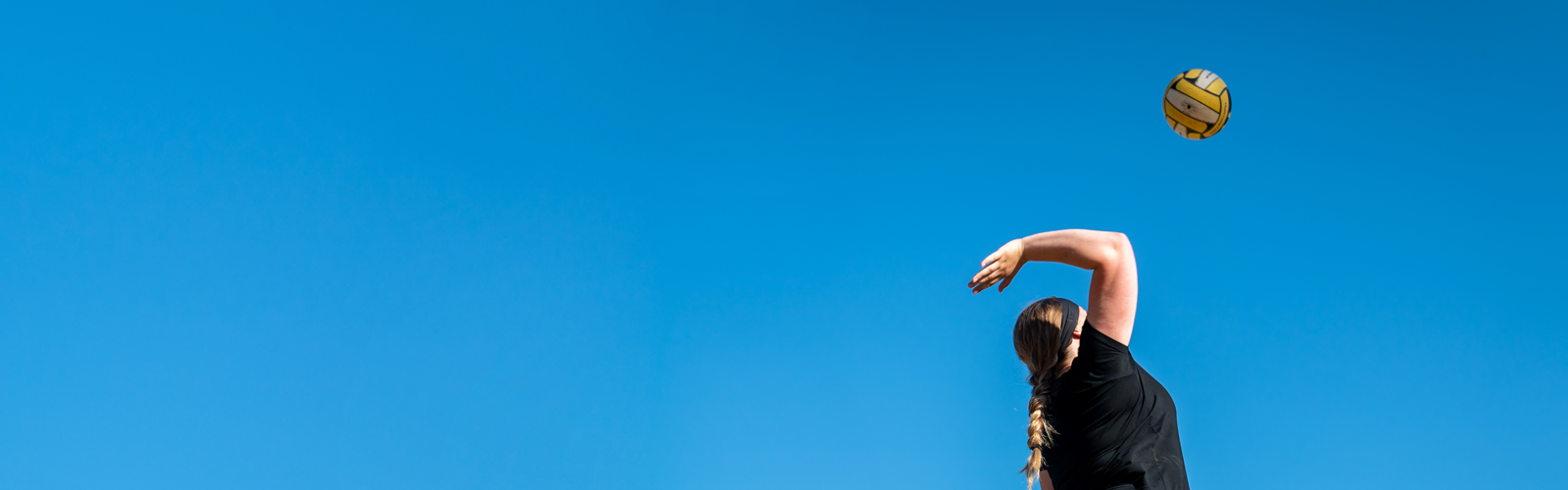 An image of a woman spiking a yellow volleyball against a bright blue sky.