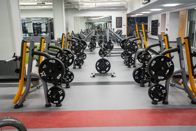 An open strength training space with a mirror on the back wall reflecting that the right and left side of this open space are symmetrically lined with multiple bench racks holding forty-five pound plates.