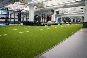 A strength and conditioning space with a turf field lining the floor. Mirrors line the walls along the right side and strength and functional equipment such as squat and bench racks, exercise balls and plyometric boxes line the center of the open space.
