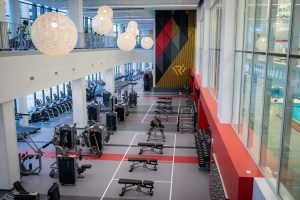 A fitness space with free weights lining the right-side wall, strength training benches and equipment distributed throughout the center and treadmills lining the left-side wall that has a street view.