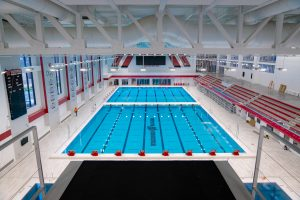 Pool with short course lanes, diving well, and spectator seating.
