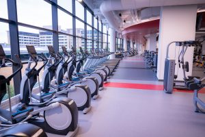 A cardio fitness space that includes ellipticals, treadmills, stationary exercise bikes and rowing machines. Open spaces available for stretching, core work and other functional fitness training.