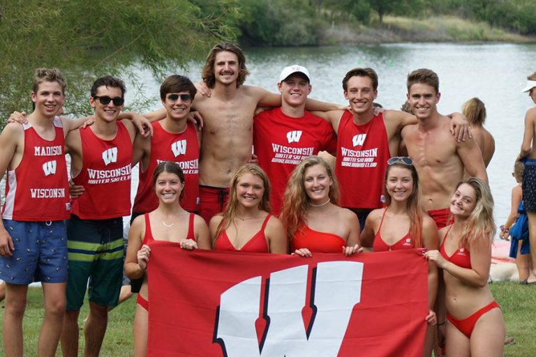 A photo of members of the Waterski and Wakeboard team holding a flat with the motion W on it
