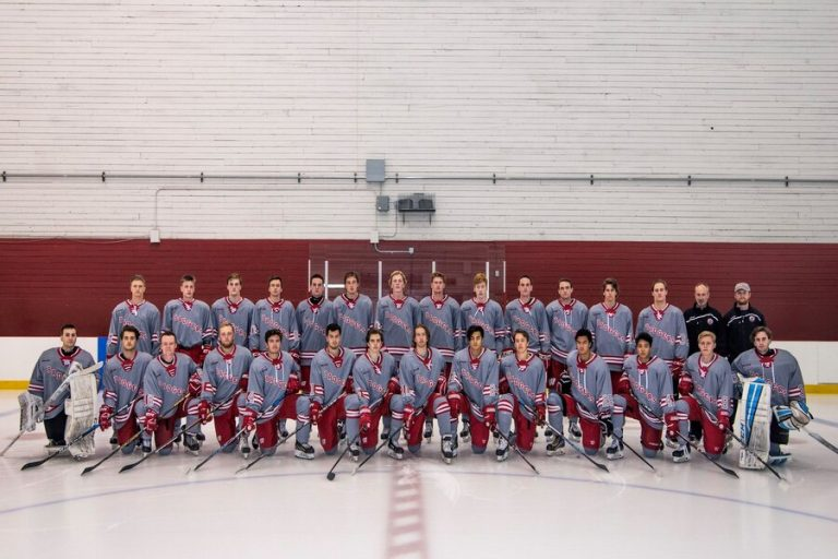 Photo of the UW Men's Ice Hockey team wearing blue and red uniforms on ice