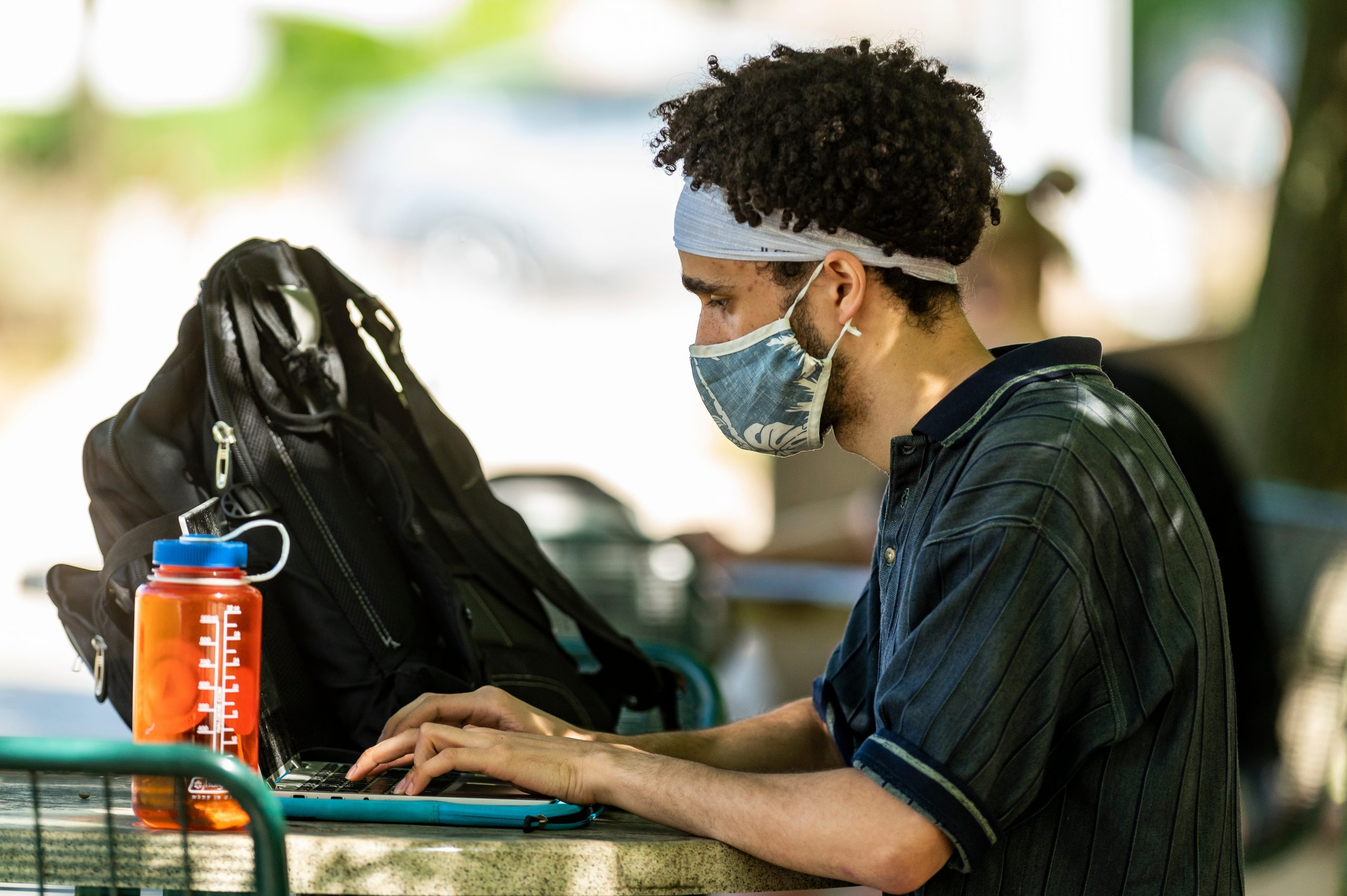 Student at their computer outside wearing a mask