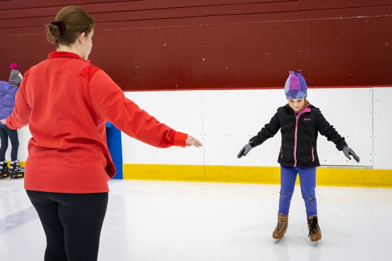 Photo of an ice skating instructor teaching a child how to balance on skates with their arms outstretched.