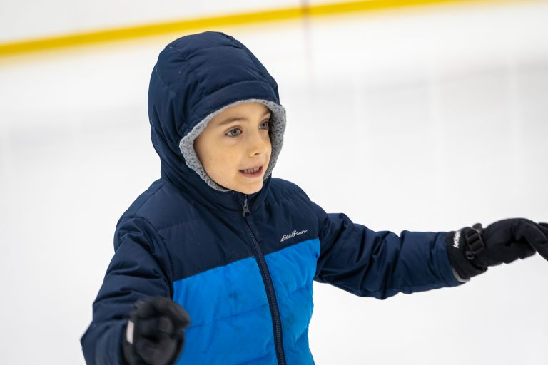A closeup photo of a child in a blue winter jacket learning how to skate.