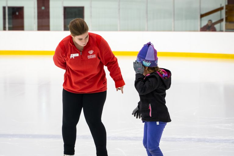 Photo of ice skating instructor teaching a child how to skate.