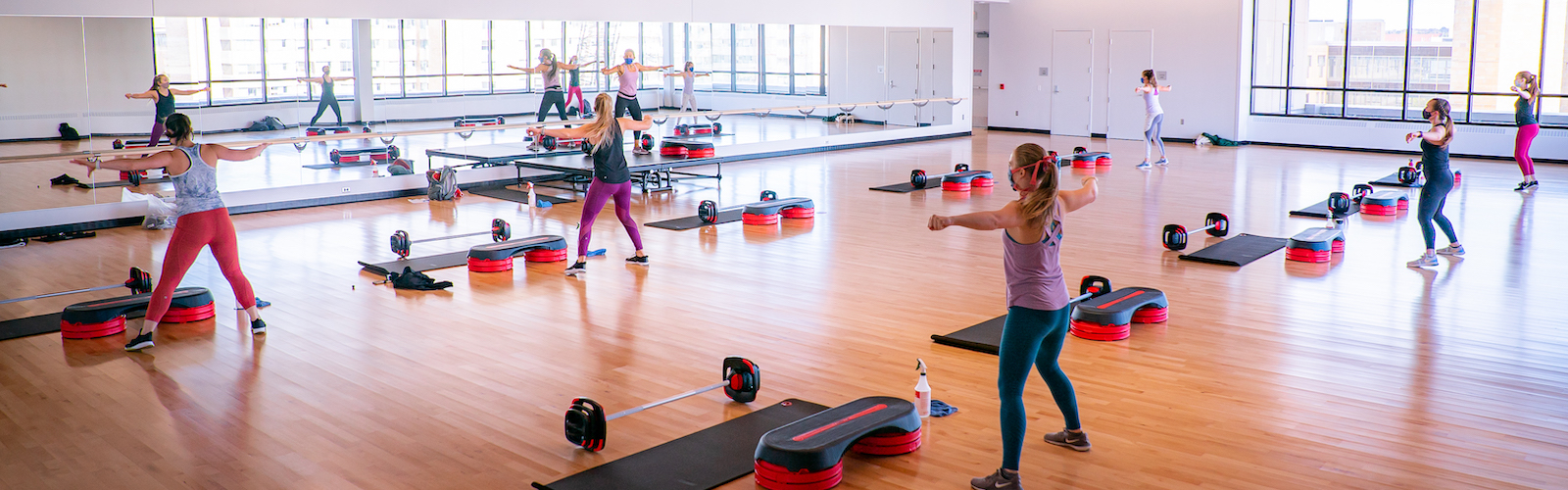 Participants standing in a weight training class performing stretches.