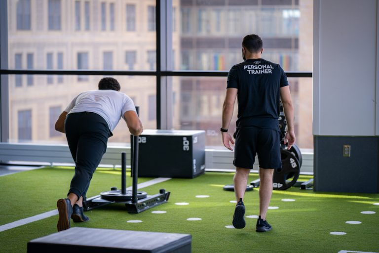 An image of a male personal trainer working with a male patron who is pushing a weighted sled.