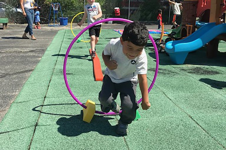 A photo of a young athlete running through a hula hoop on a playground