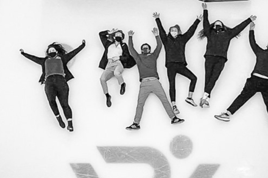 A black and white image of RecWell employees laying down on the ice rink and posing for a top down photo