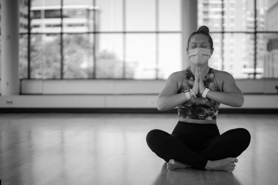 A black and white photo of a woman meditating in a room alone