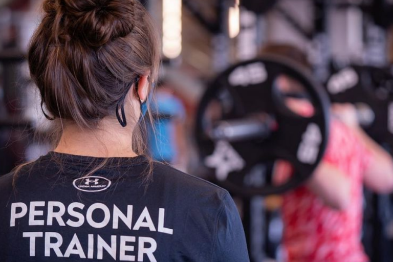 A female personal trainer looking on as a man does weighted squats