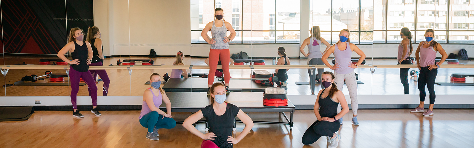 An image of six group fitness instructors wearing masks in front of a stage used to teach classes