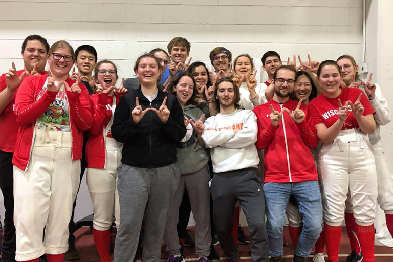 Photo of fencing team throwing up a W.