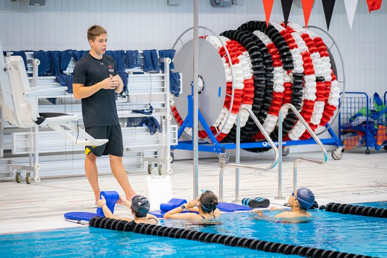 A photo of an instructor standing on the side of the pool telling three swimmers in the water what to do