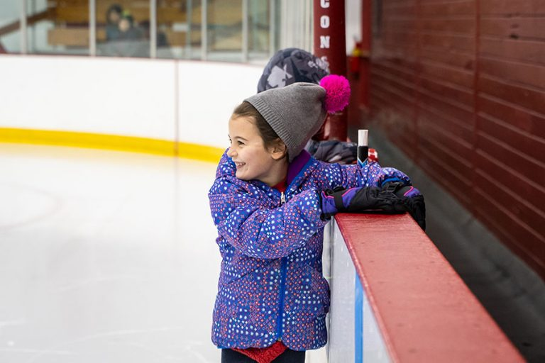 A photo of a Jr. Active Badger hanging on to the wall in the ice rink, smiling during their ice skating lesson